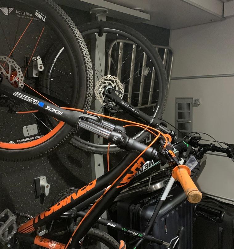 Två cyklar hänger i krokar i taket på ett tåg.
