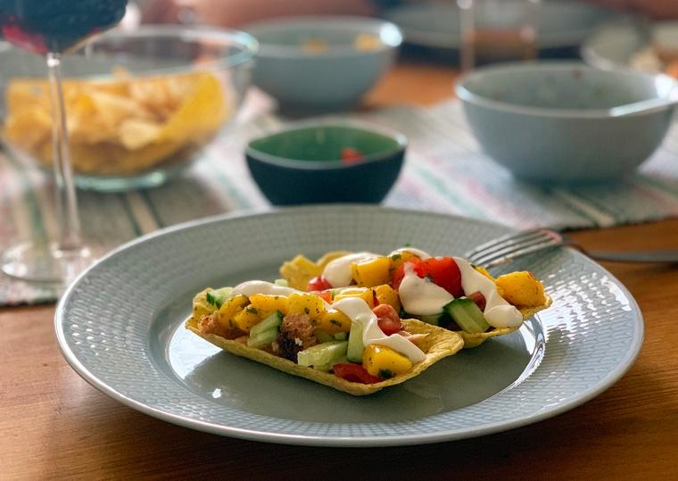 Ett blått fat med två färgglada tacos.