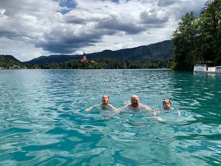 En vuxen och två barn simmar i en sjö.