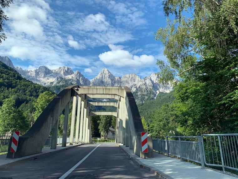 En väg med en bro och en bergskedja i bakgrunden.