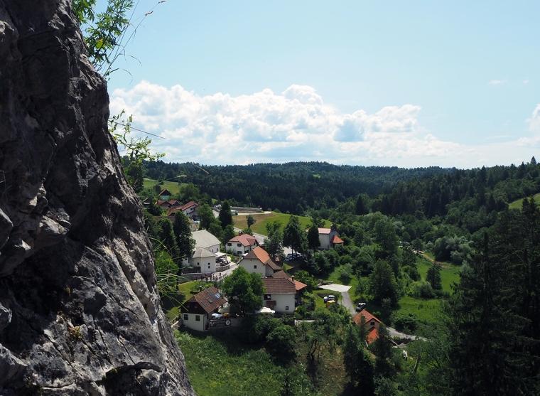 Utsikt med gröna skogar och små vita hus.
