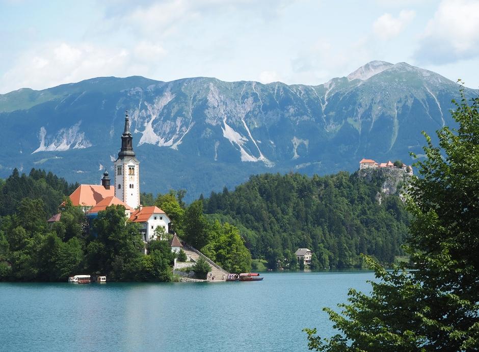 Grön sjö med en ö med en vit kyrka och berg i bakgrunden.