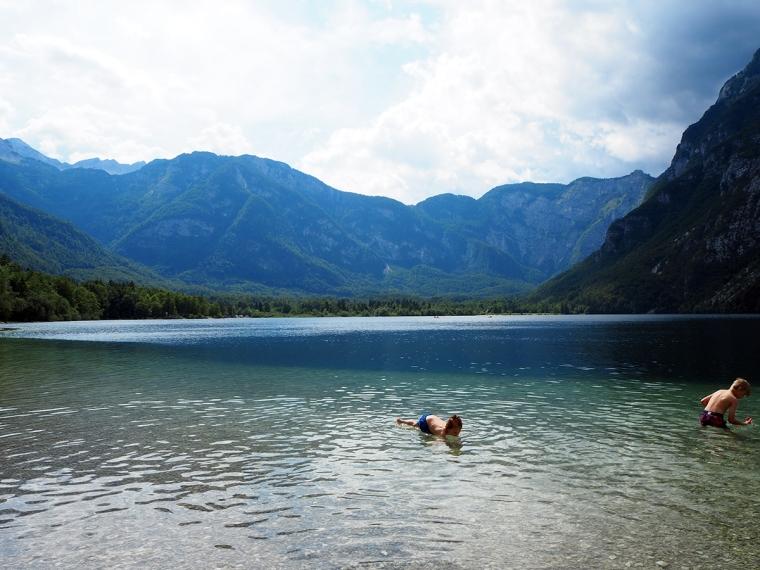 Två barn badar i en grön sjö med berg i bakgrunden.