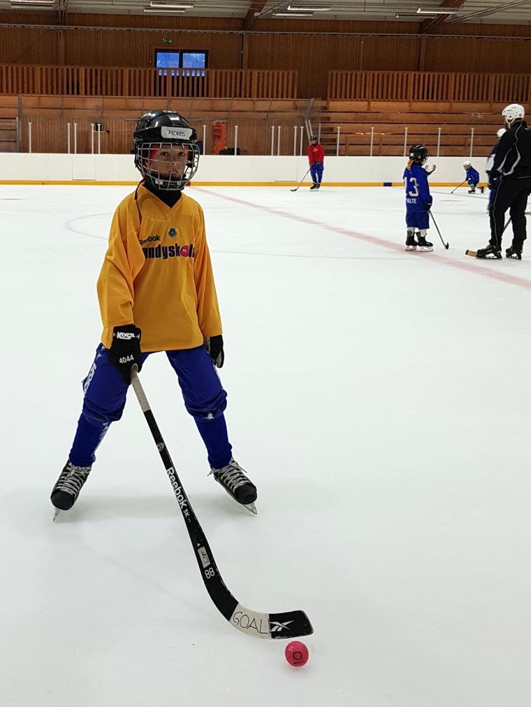Ett barn står med bandyutrustning på is.