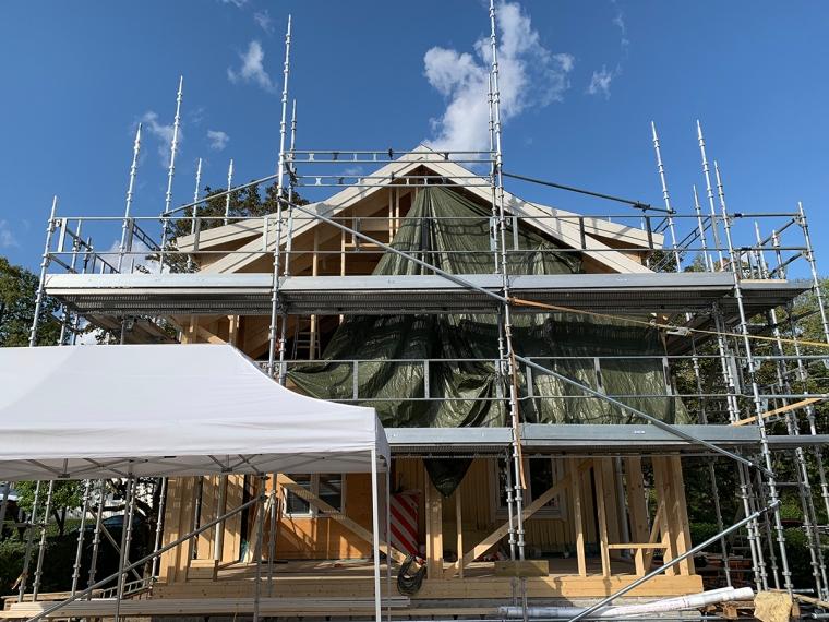 Byggställningar med ett träsklett till hus bakom.