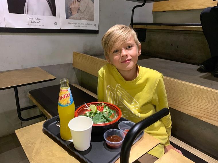 Ett barn sitter med en bricka med mat framför sig.