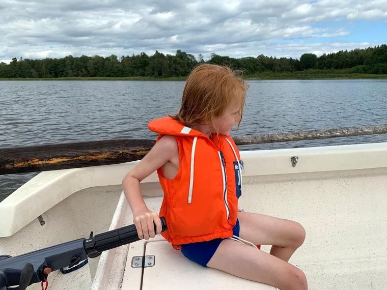 Ett barn i flytväst styr en motorbåt.