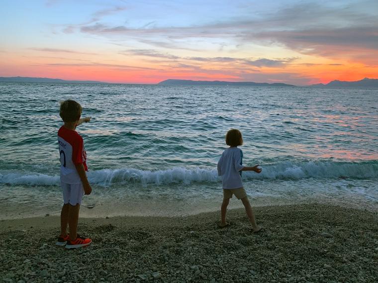 Två barn på en stenstrand i solnedgång.