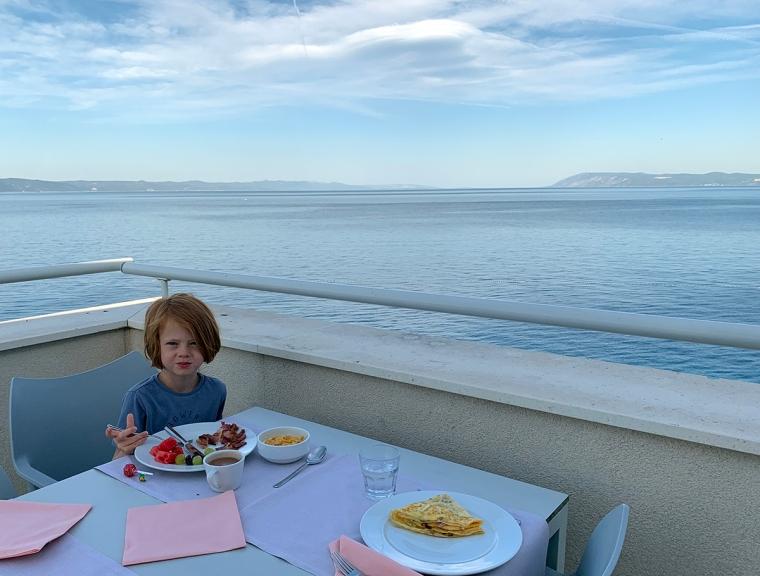 Ett barn sitter på en balkong med havet i bakgrunden.