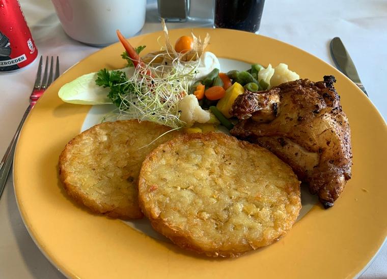 En tallrik med en halv grillad kyckling, potatisbullar och grönsaker.