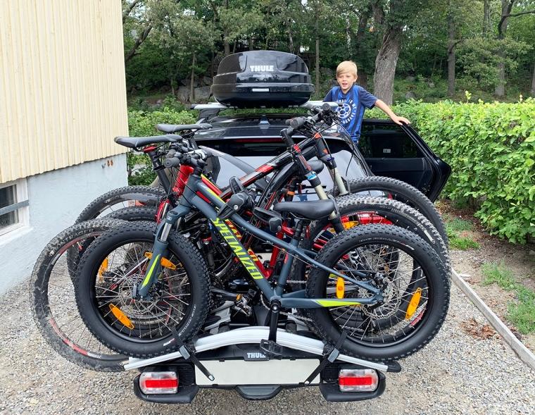 En kombibil med takbox och fyra cyklar där bak.
