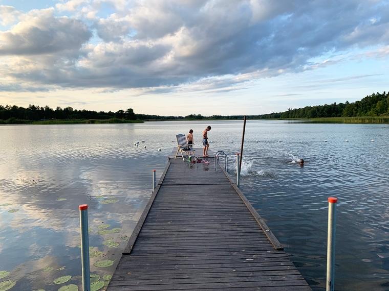 Två barn på en brygga i en sjö.