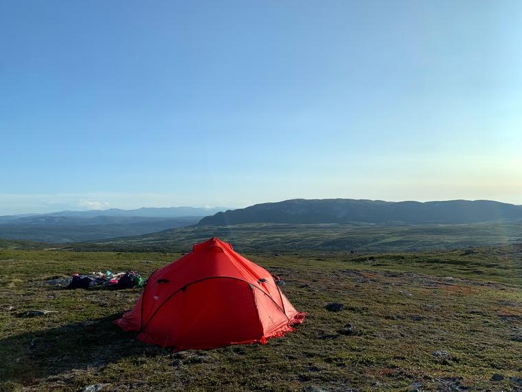 Ett rött tält med utsikt över berg.
