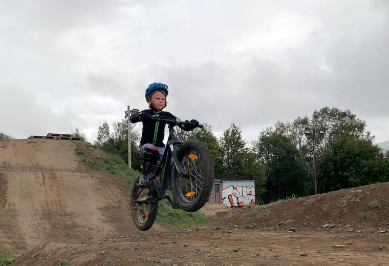 Ett barn hoppar med en cykel i en dirt park.