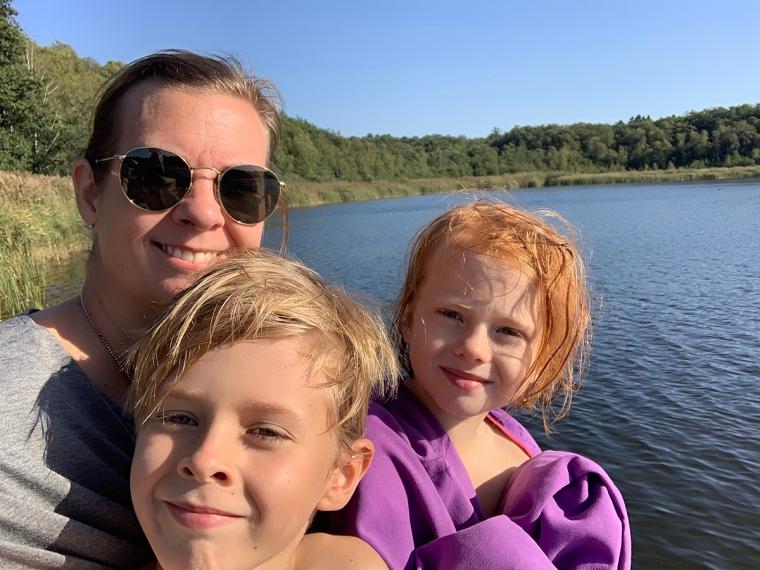 En kvinna och två barn vid en sjö.