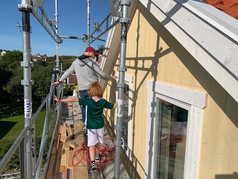 En man och ett barn på byggställningar.
