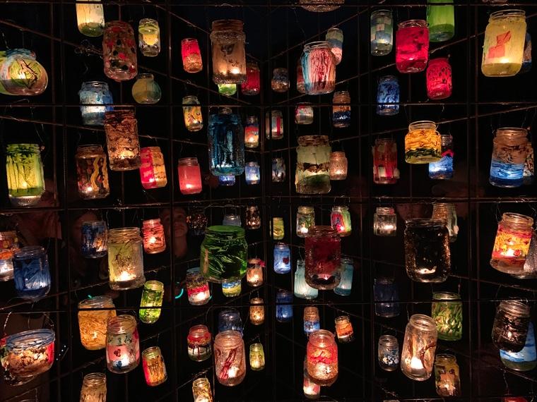 Målade glasburkar med värmeljus i.