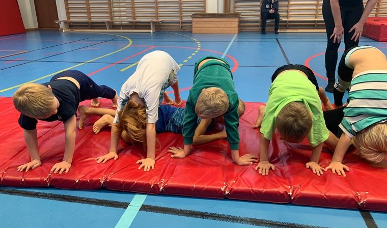 Ett gäng ungar på en gymnastikmatta.