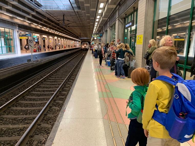 Två barn på en perrong och som väntar på tåget.