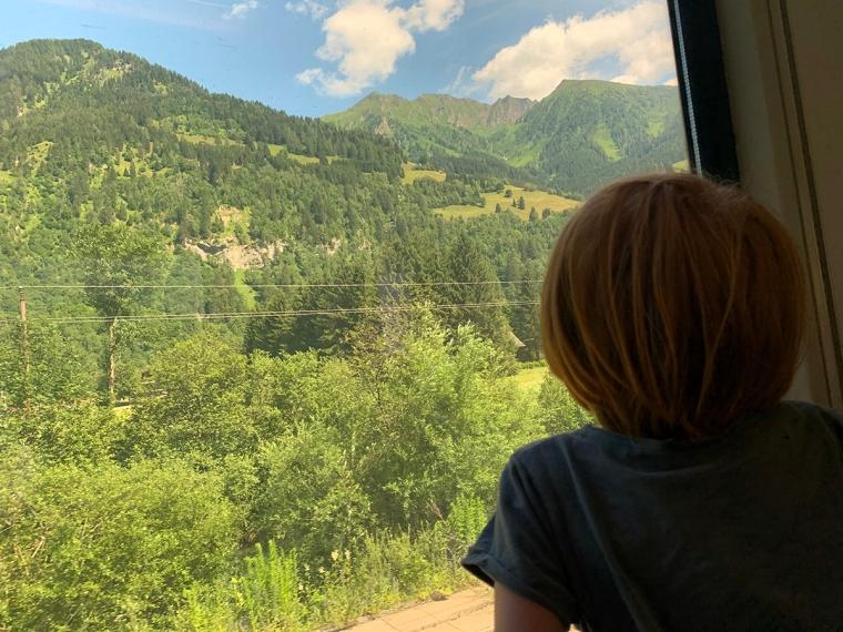 Ett barn tittat ur från ett tågfönster.