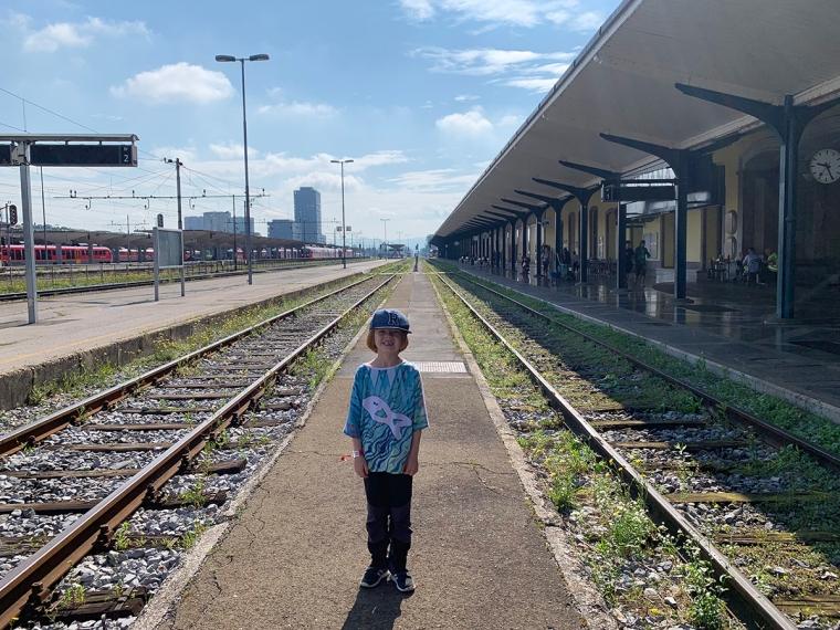 Ett barn står på en perrong.