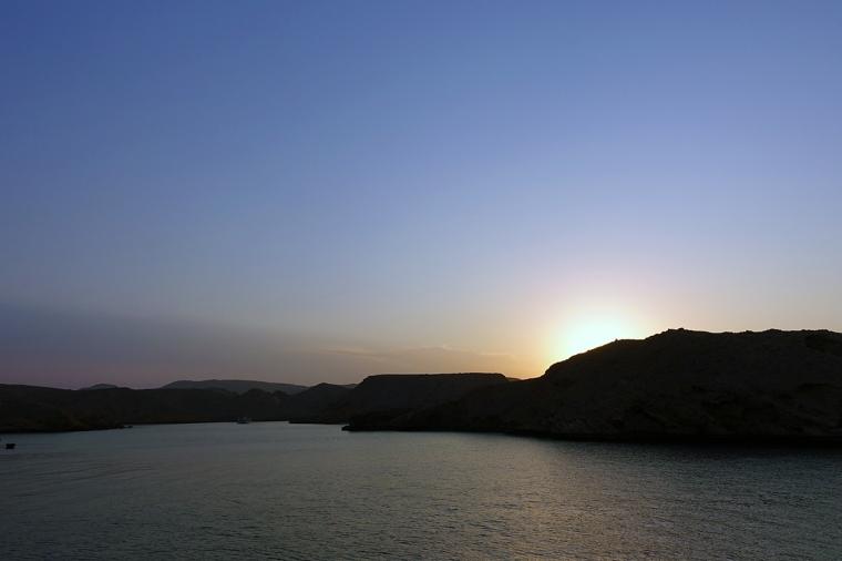Solnedgång bakom en klippa i vatttnet.