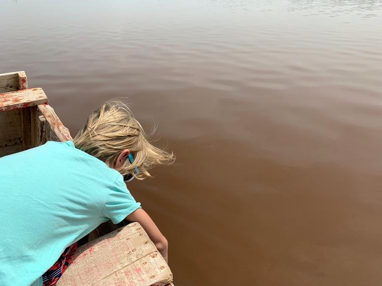Ett barn ligger på mage i en träbåt och tittar ner i vatten.