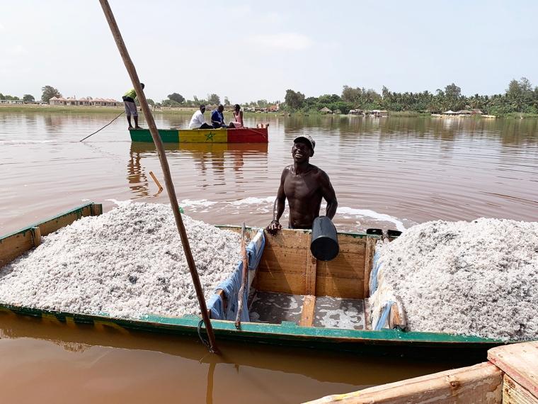 En man står med vatten till midjan och framför honom en grund trädbåt full med salt.