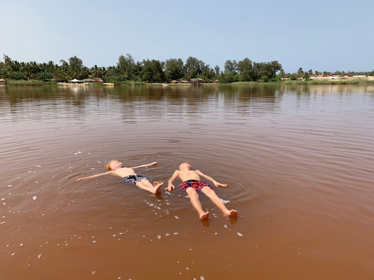 Två barn ligger på rygg och flyter i vattnet.
