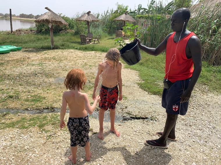 En man med en hink häller vatten över två barn.
