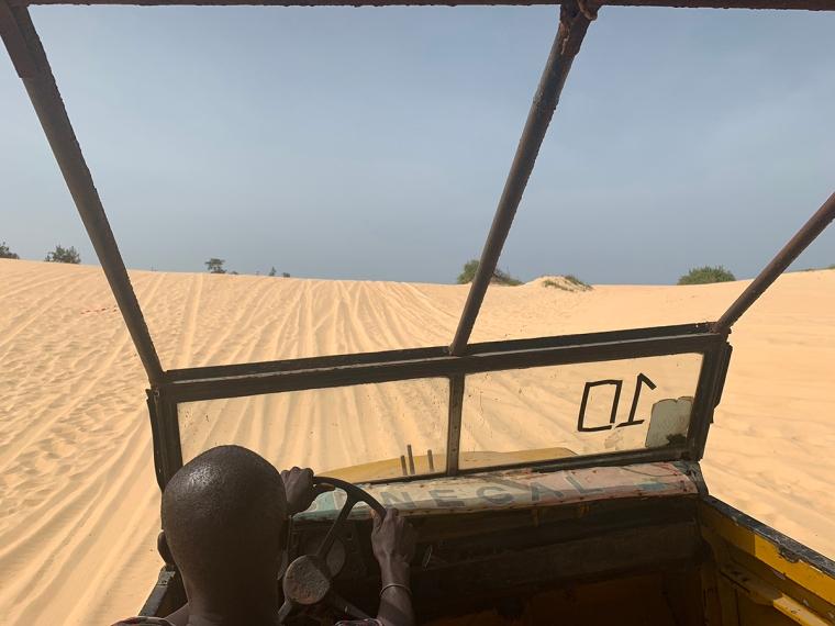 En jeep som kör över en sanddyn.