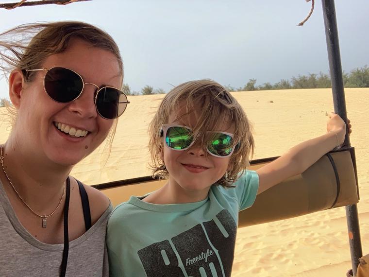 En kvinna och ett barn sitter i en öppen jeep.