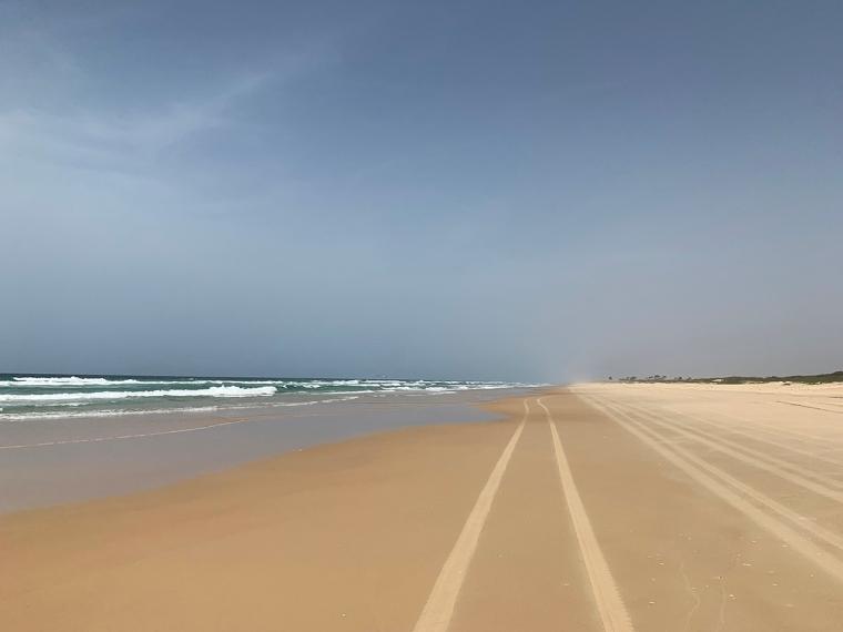 En lång sandstrand med hjulspår.