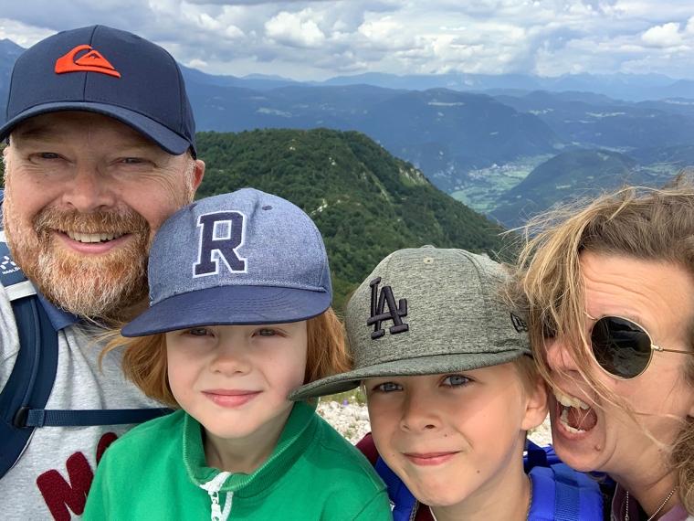 En man, en kvinna och två barn med berg i bakgrunden.