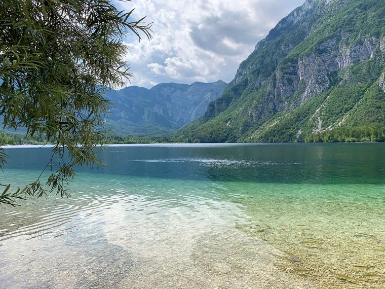 En grön sjö med berg i bakgrunden.