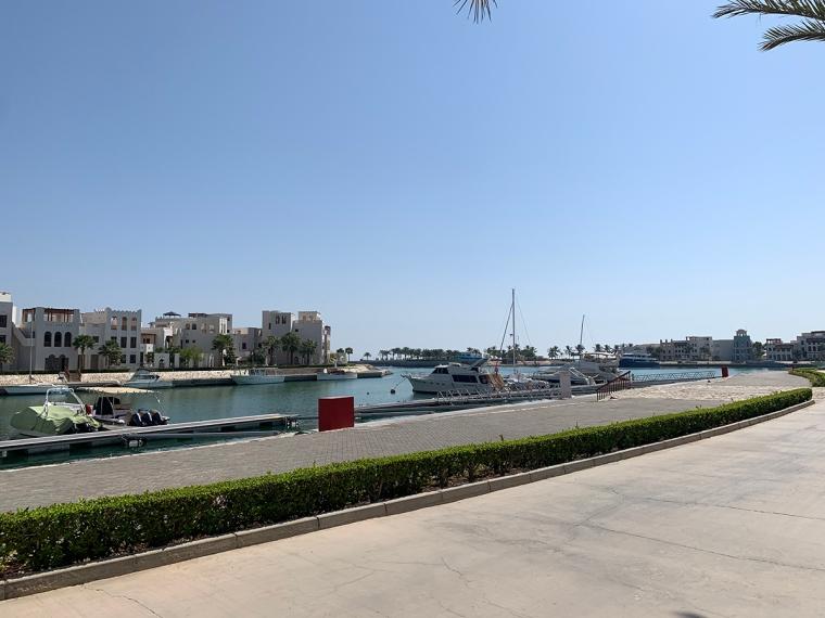 Strandpromenad i en marina med några båtar.
