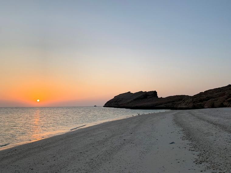 En strand med en snolnedgång i havet.
