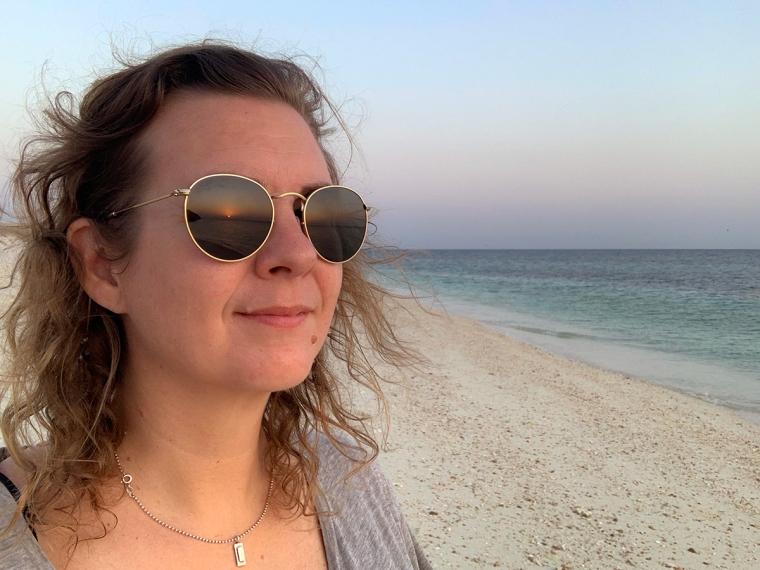 En tjej med solglasögon där en solnedgång speglas.