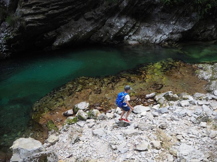 Ett barn vid nere vid ett grönt vattendrag.