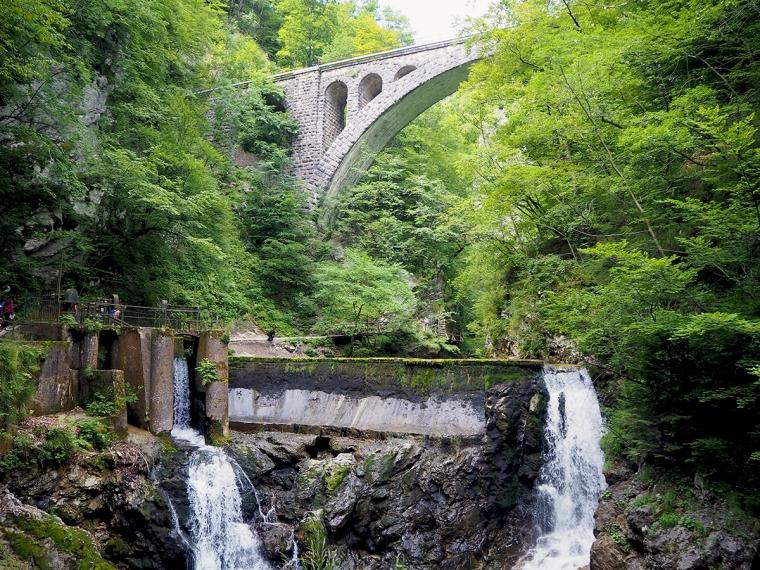 En sten bro över en damm där vatten forsar ner.