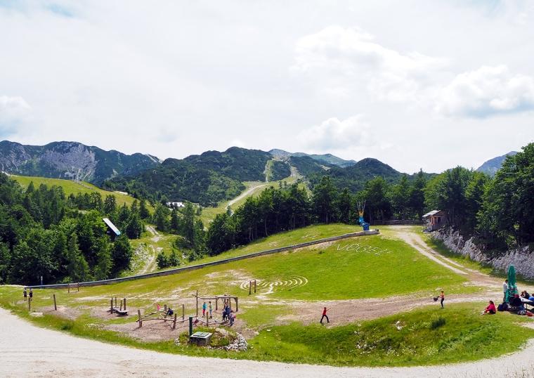 En gräsplan med olika klätterställningar och berg i bakgrunden.
