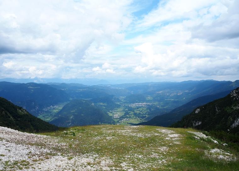 Utsikt från ett berg, dalgång och berg i bakgrunden.