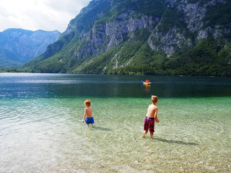 Två barn badar i en grön sjö där det också syns en kajak.