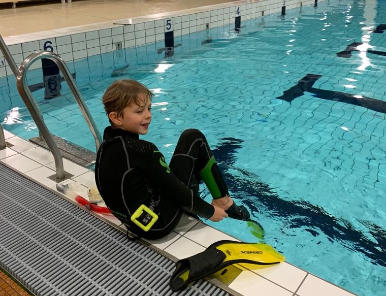 Ett barn i våtdräkt på en poolkant.