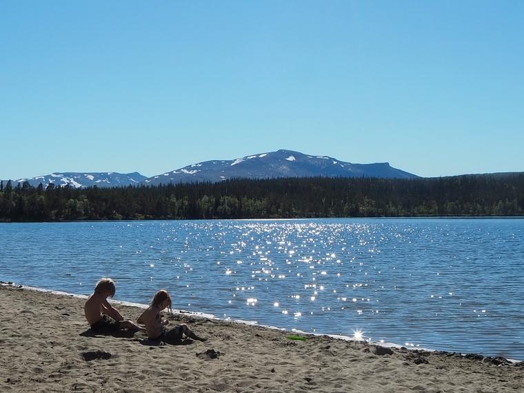 Två barn sitter på en sandstrand med berg i bakgrunden.