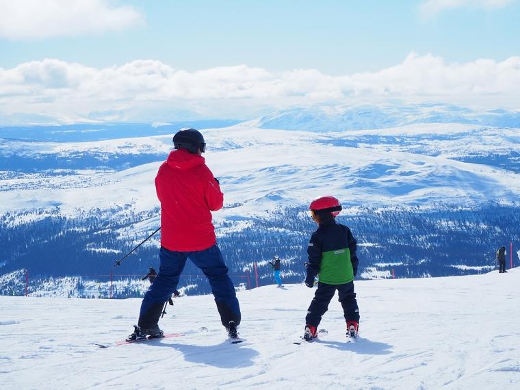 En man och ett barn står högst upp i en skidbacke. Fjäll i bakgrunden.
