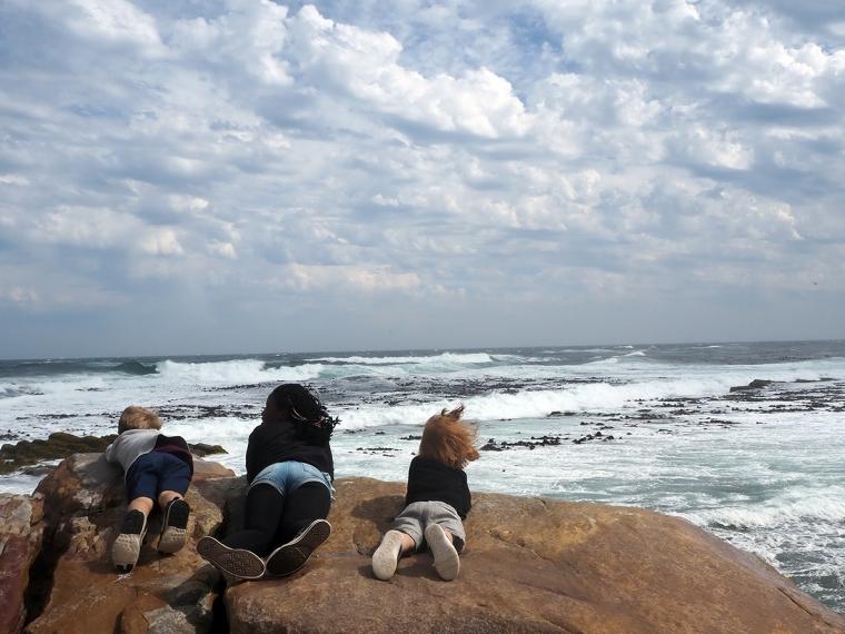 Tre barn som ligger på mage och kikar ut över ett stormande hav.