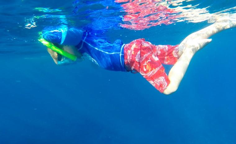 Ett barn med mask och snorkel i blåvatten.