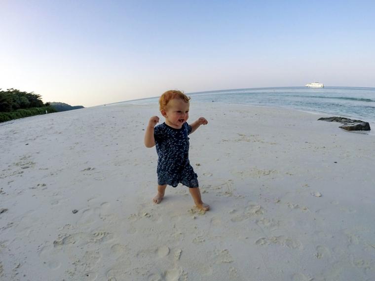 Ett litet barn går på en vit sandstrand.