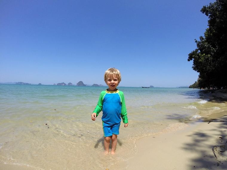 Ett barn står i vattenbrynet på en sandstrand.